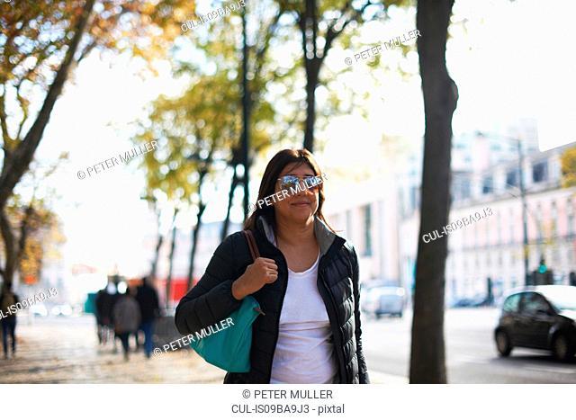 Woman wearing sunglasses walking in street, Lisbon, Portugal, Europe