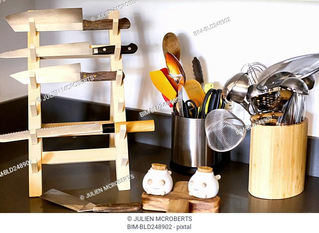 Knives in rack near kitchen utensils