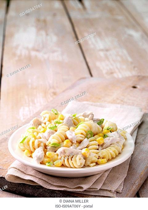 Still life of chicken and sweetcorn pasta with spring onion garnish in a bowl