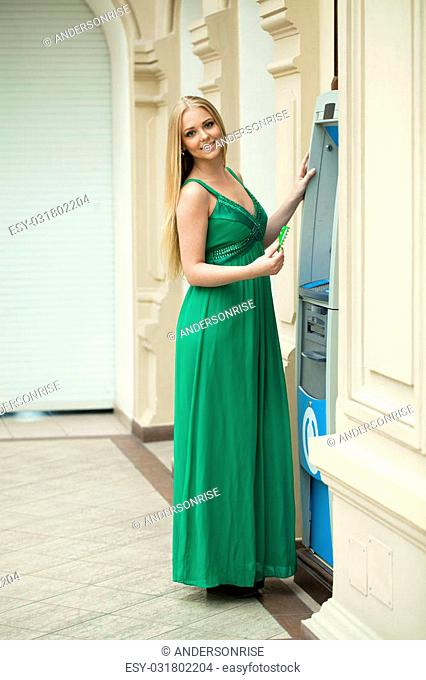 Happy Blonde young lady using an automated teller machine. Woman in green dress withdrawing money or checking account balance