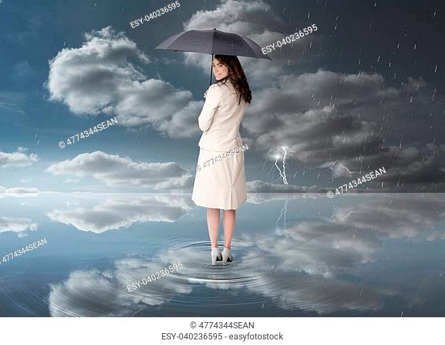 Businesswoman holding a black umbrella during stormy weather