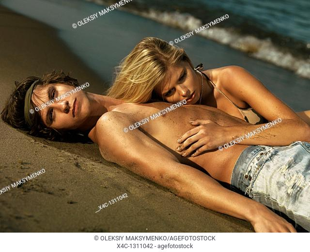 Young woman in bkini and a young man in jeans lying on the shore