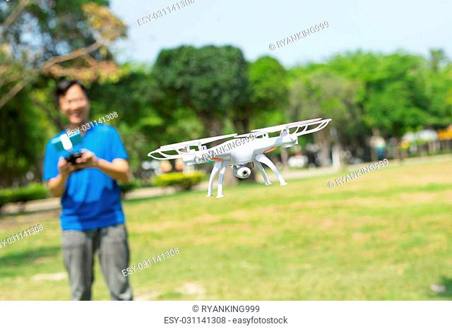 man play drone in the park happily, asian