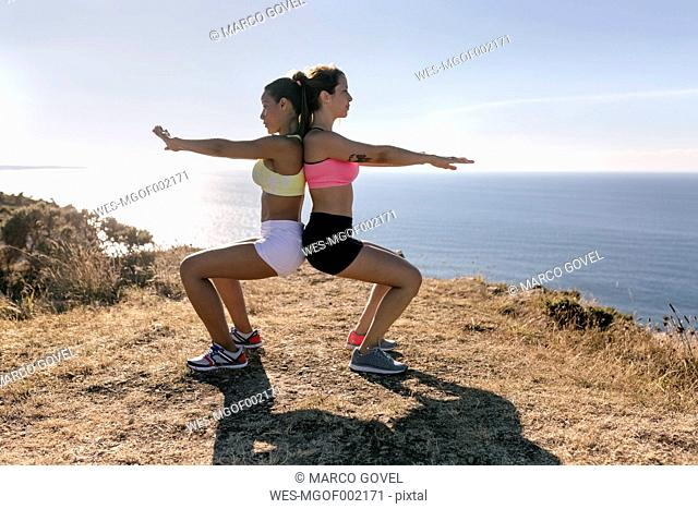 Spain, Asturias, two sportswomen training on the coast, back to back