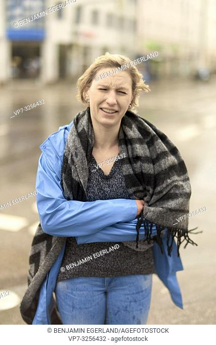 woman outdoors in city in bad weather, in Munich, Germany
