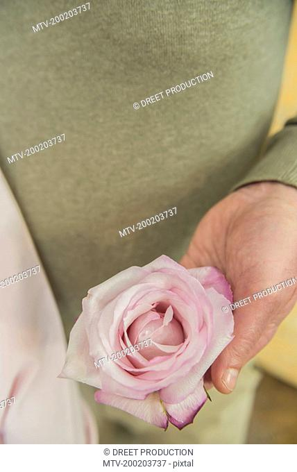 Mature couple holding rose, close up