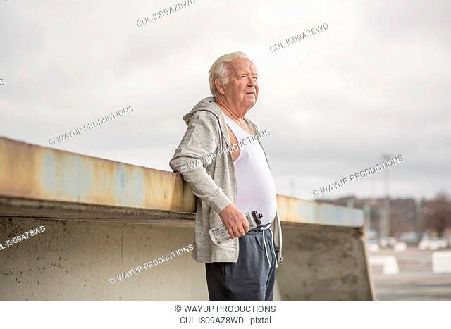 Man wearing sports clothes holding water bottle looking away