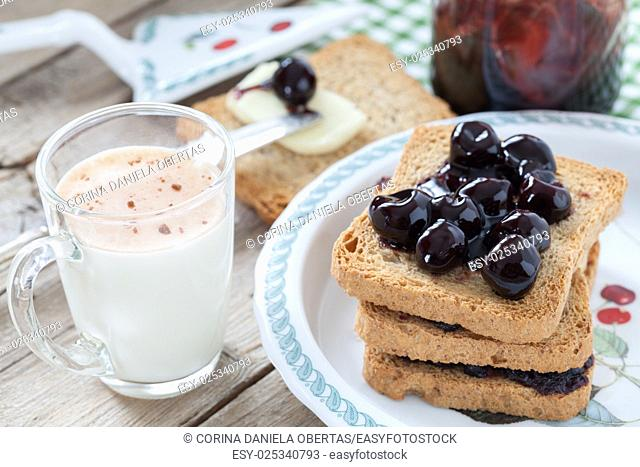 Breakfast with rusks, sour cherries jam, butter and milk