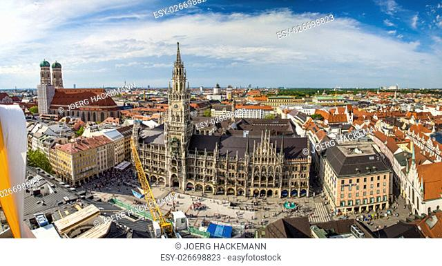 Beautiful super wide-angle sunny aerial view of Munich, Bayern, Bavaria, Germany with skyline and scenery beyond the city, seen from the observation deck of St