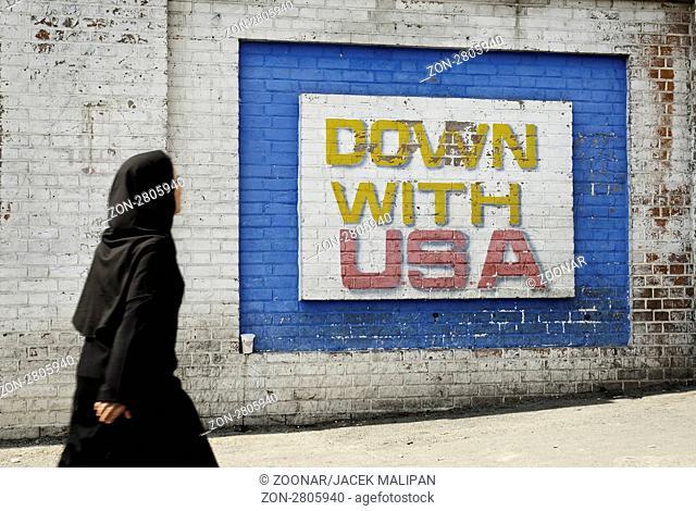 black veil wearing muslim woman walking past anti american mural outside old american embassy in teheran, iran