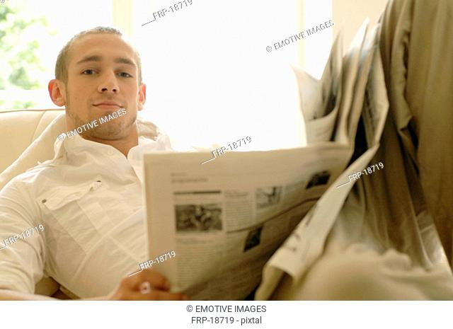 Young man reading newspaper on couch