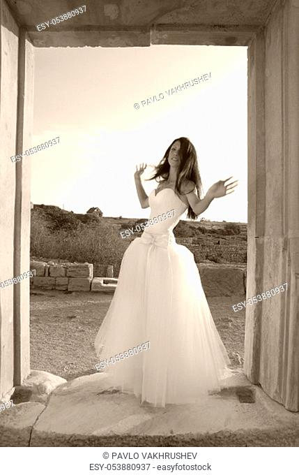 Beautiful bride in the white dress at greece ancient door. Black and white, sepia