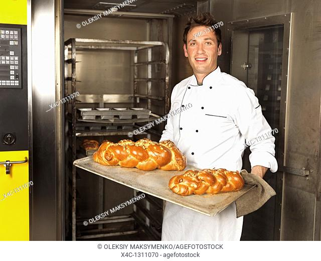 Portrait of a baker holding a tray with freshly baked sweet braided breads challah right out of the oven
