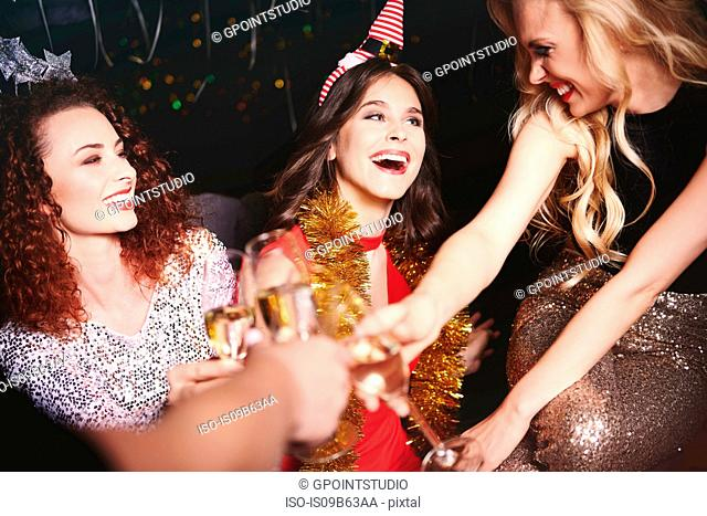 Three women sitting together at party, holding champagne glasses, making a toast
