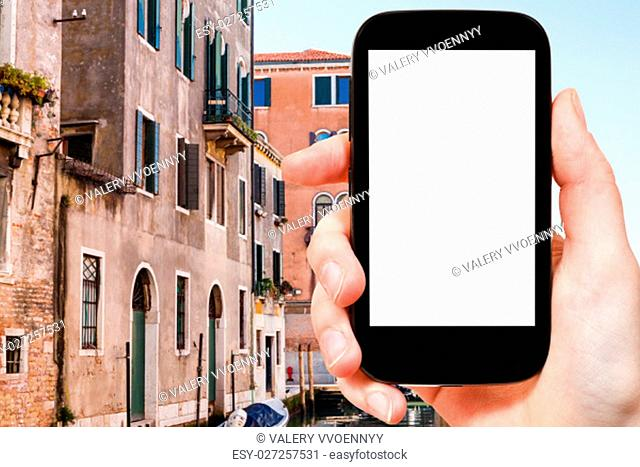 travel concept - tourist photographs houses in Venice city on smartphone with cut out screen with blank place for advertising in Italy