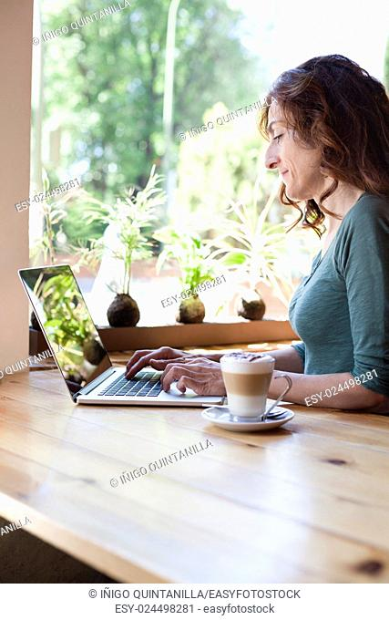 woman with green shirt typing on keyboard pc laptop and cappuccino coffee cup ready thinking on light brown wooden table