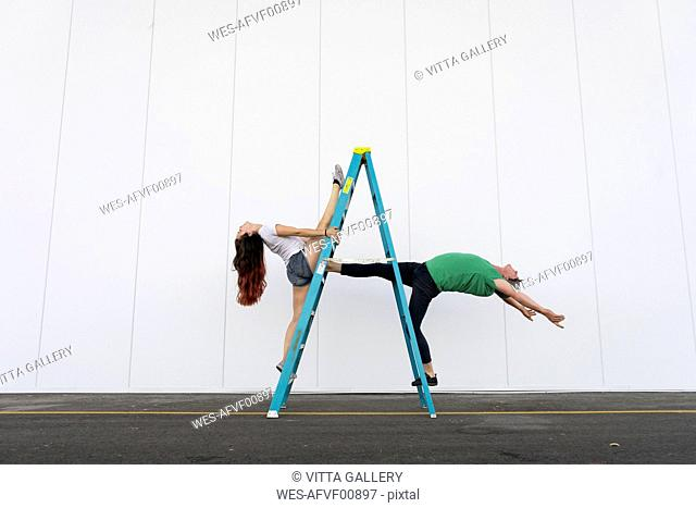 Two acrobats doing tricks on a ladder