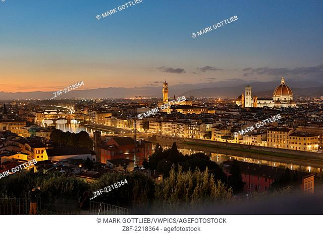 Overlooking Florence, Italy. Taken from Michelangelo's Piazza at dusk. Beautiful lighting. Blue sky. Duomo Cathederal, Ponte Vecchio Bridge and Tower at Palazzo...