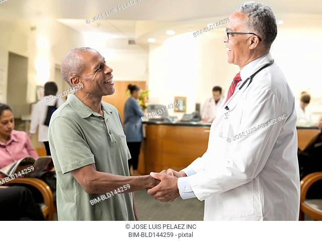Doctor shaking hand of patient in hospital