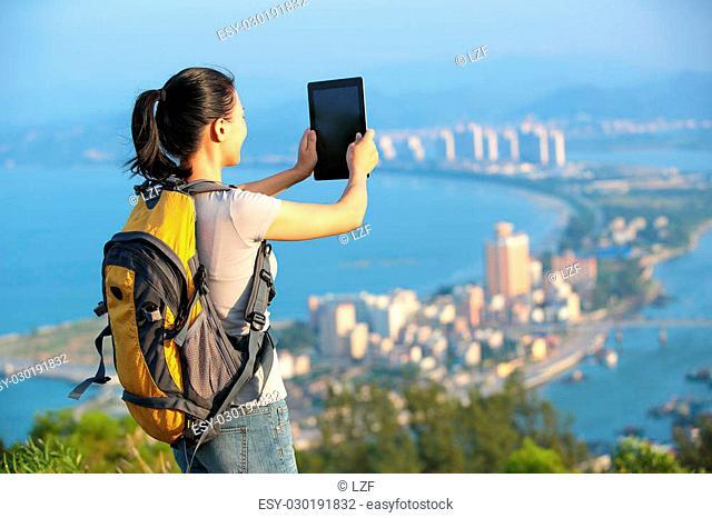 young asian woman hiker use digital tablet seaside mountain peak