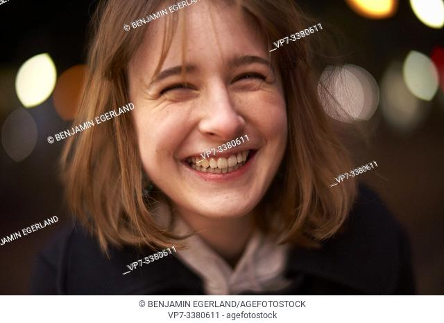 closeup woman laughing at night in Berlin, Germany