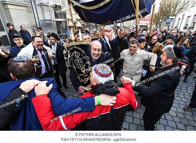 dpatop - 10 November 2019, Baden-Wuerttemberg, Konstanz: Hundreds of people of Jewish faith walk and dance with their Torah rolls from the old synagogue to the...