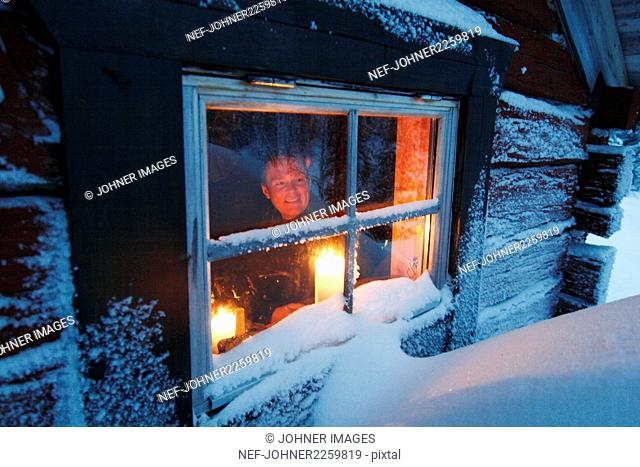 Man looking through window of log cabin