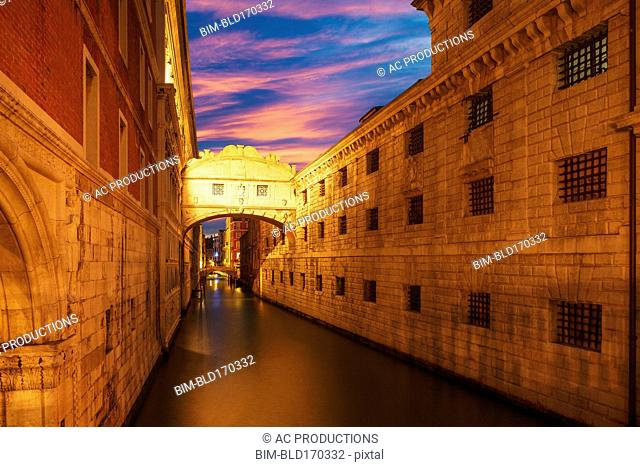 Bridge over Venice canal under sunset sky