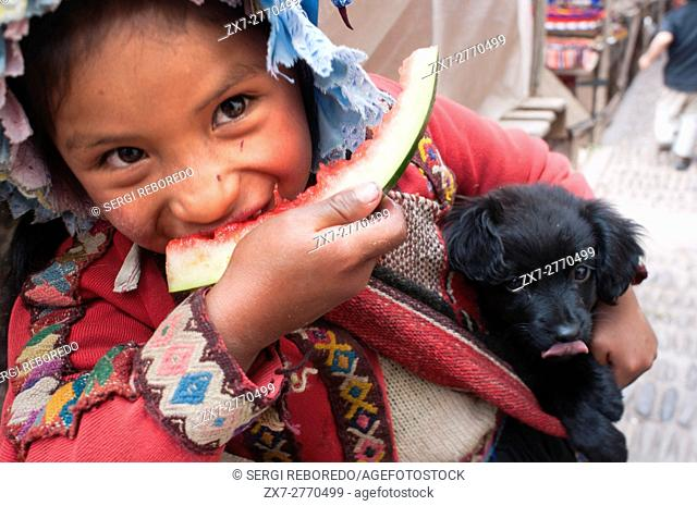 Sacred Valley, Pisac, Peru. A girl dressed in a traditional costume eating a piece of watermelon in Pisac Sunday market day. Pisac. Sacred Valley