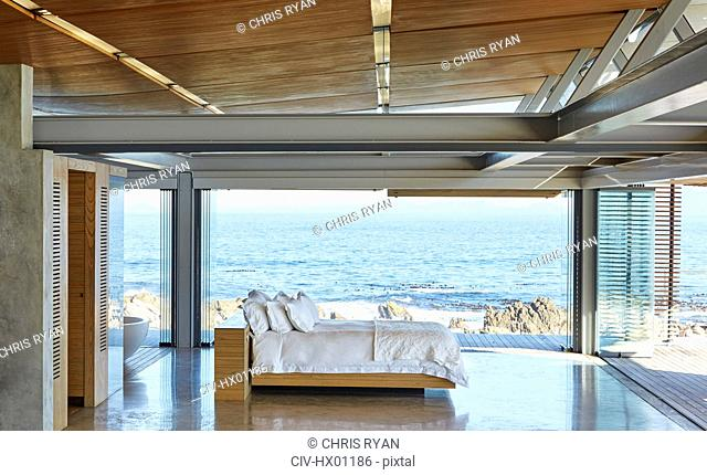 Modern luxury bed open to patio with sunny ocean view
