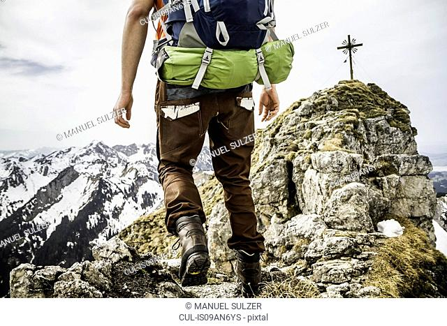 Cropped shot of young male hiker on peak of Klammspitze mountain, Oberammergau, Bavaria, Germany