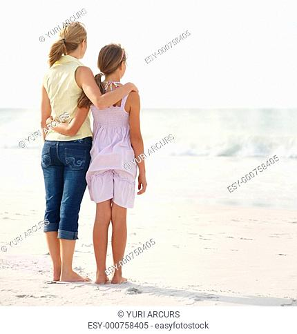 Rear view of a mother and teenaged daughter standing together on the beach