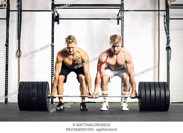 Two young men in gym lifting weights