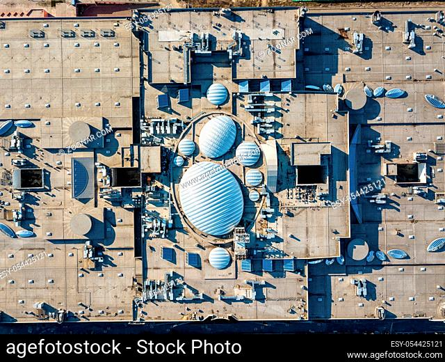 The shopping center roof, top view srtictly above - construction of roof equipment with antennas, ventilation outlets and other roof installation