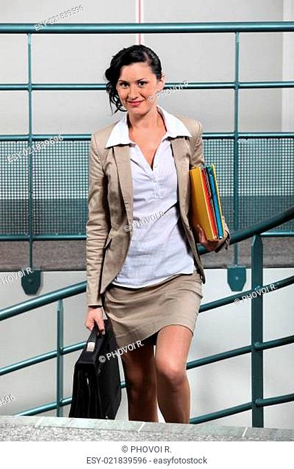 young businesswoman with briefcase going upstairs