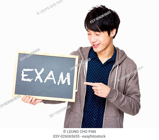 Young man finger point to chalkboard showing a word exam