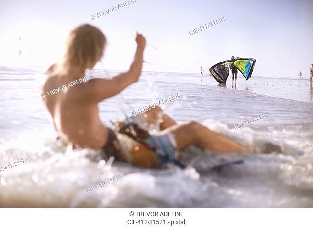 Man ready to kiteboard in ocean surf