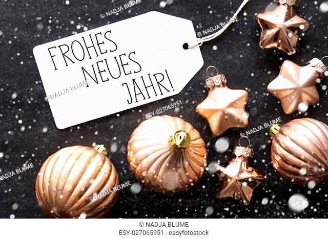 Label With German Text Frohes Neues Jahr Means Happy New Year. Bronze Christmas Tree Balls On Black Paper Background With Snowflakes
