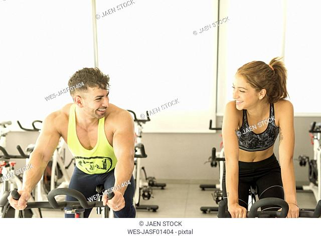 Young man and woman exercising on spinning bikes in gym