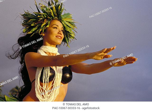 Woman hula with shell lei, coconut top, ti leaf haku arms outstretched to sky