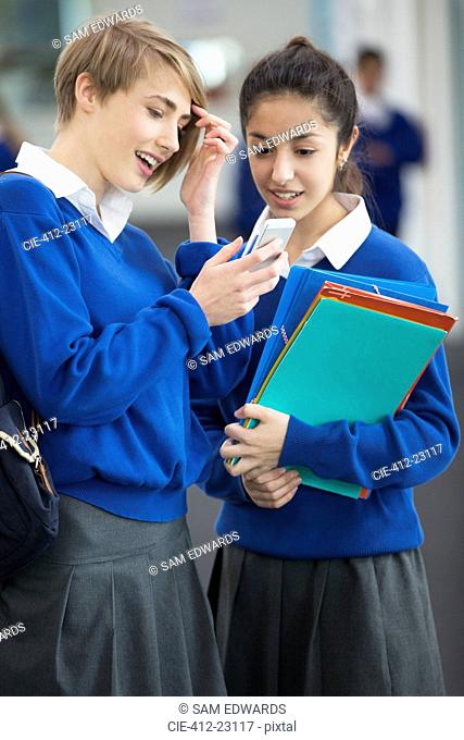 Two smiling female students wearing school uniforms using smartphone