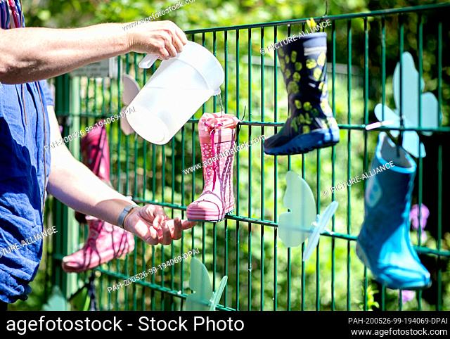 26 May 2020, Lower Saxony, Oldenburg: Colourful rubber boots hang on the fence of a kindergarten in the district of Bümmerstede as a sign of solidarity