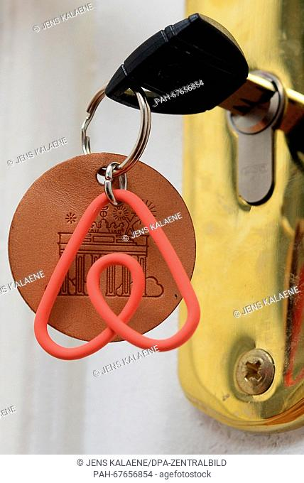 A keychain with the logo of the online platform and community marketplace for private accommodations, Airbnb, hangs on a key in the door of a vacation apartment...