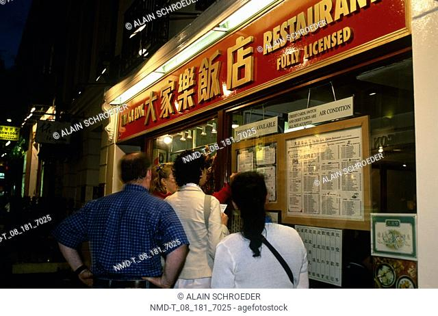 Four people in front of restaurant, Chinatown, London, England