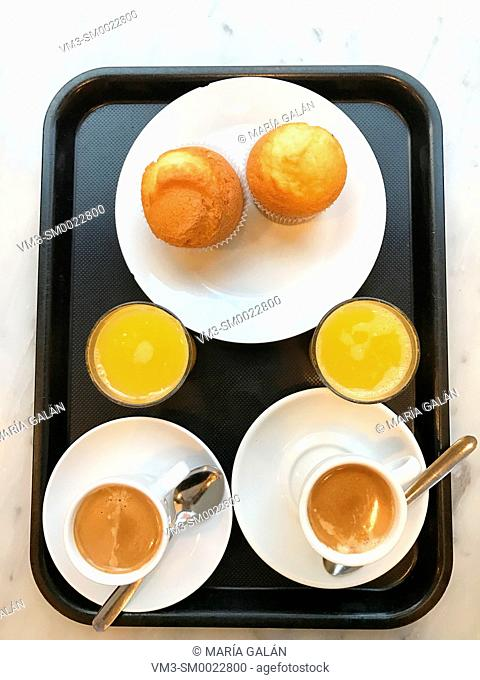Two cups of coffee with sponge cakes and two orange juices. View from above