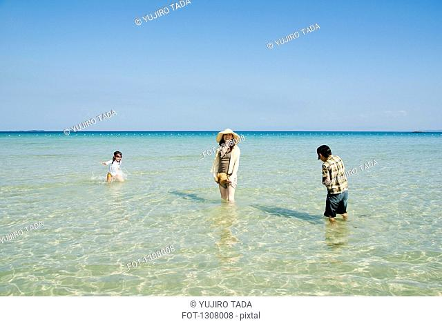 Mother with daughter and son enjoying at beach