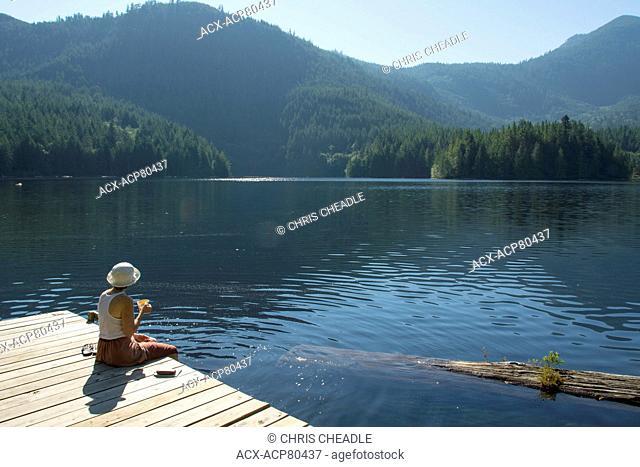 Woamn enjoying morning tea on Klein Lake near Egmont, , Sunshine Coast, British Columbia, CanadaBritish Columbia, Canada