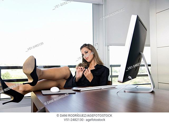 Woman in office filing nails in front of the coumputer with legs on the table