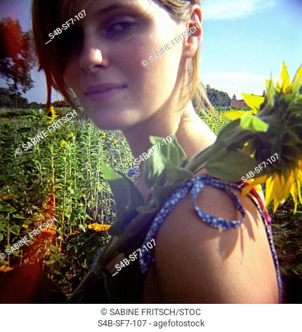 Teenage girl holding sunflower, Bavaria, Germany