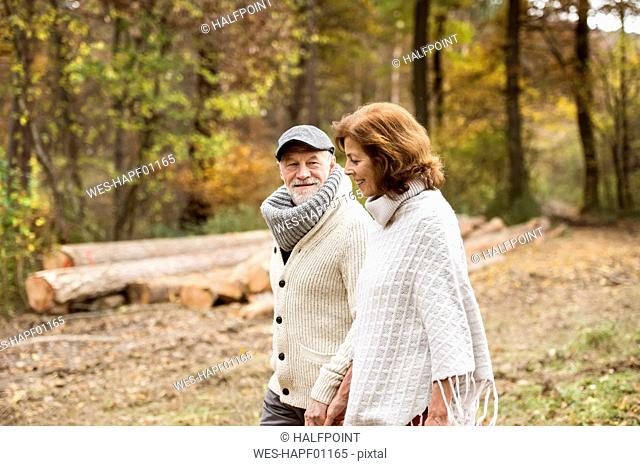 Senior couple walking in the woods in autumn